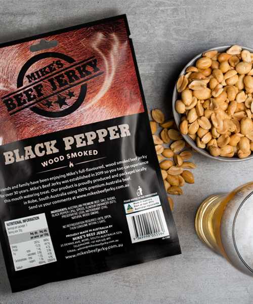 Mike's Beef Jerky. Arial photo of back of pack next to a bowl of nuts and a glass or beer.